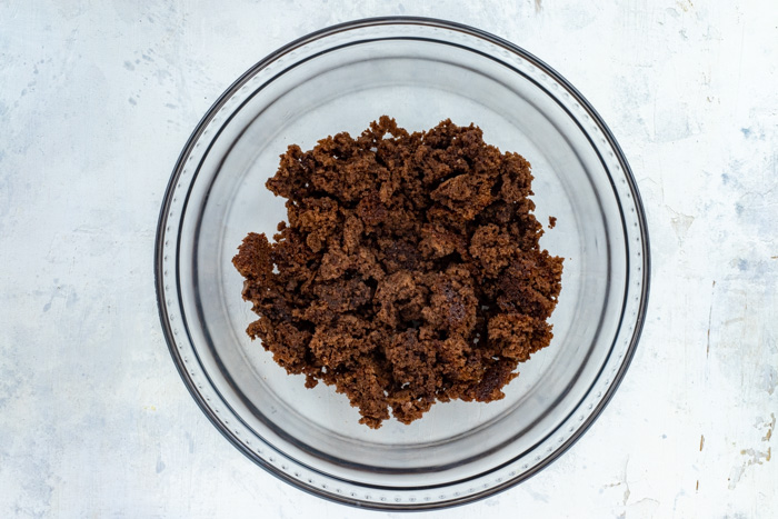 Crumbled brownies in the bottom of a glass trifle bowl on a white surface