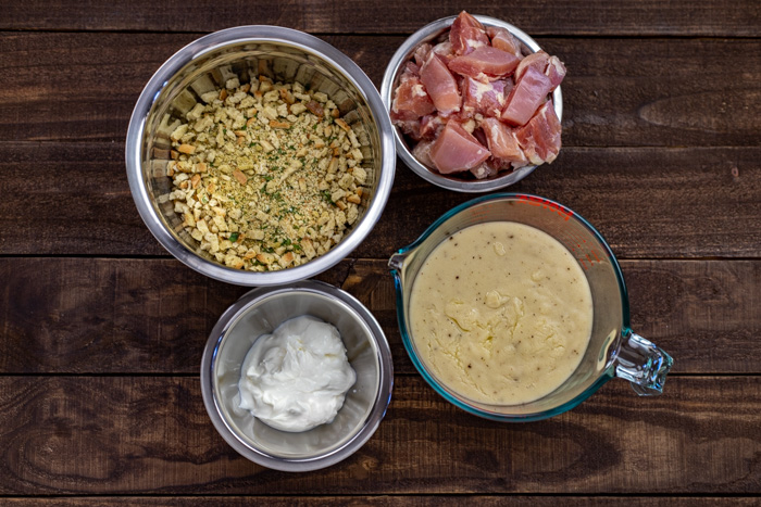 Ingredients for easy chicken casserole in stainless steel bowls on a wooden surface