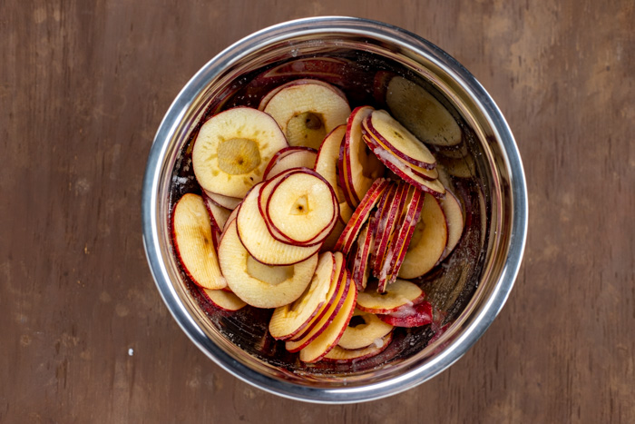 Sliced apples with lemon juice and sugar in a stainless steel bowl on a wooden surface