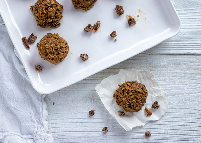 Almond-Date energy ball on a piece of parchment paper with a tray of energy balls behind all on a white wooden surface