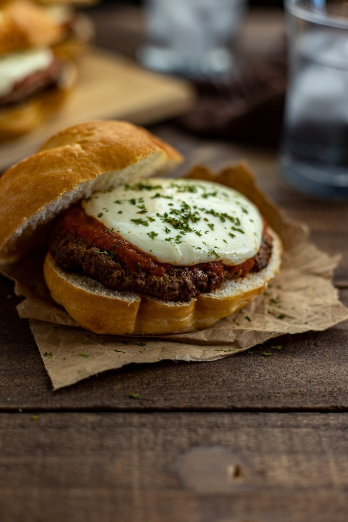 Pizza burger on a piece of parchment paper with a bamboo tray of burgers behind and a glass of ice water with a brown and white towel all on a wooden surface (vertical)