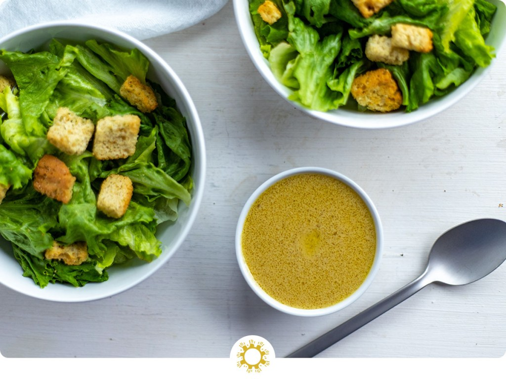 Dijon vinaigrette dressing in a small round white bowl next to two round white bowls of salad, a stainless steel spoon, and a white towel all on a white and grey surface (with logo overlay)