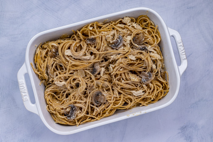 Chicken tetrazzini and noodles in a white casserole dish on a white and blue surface
