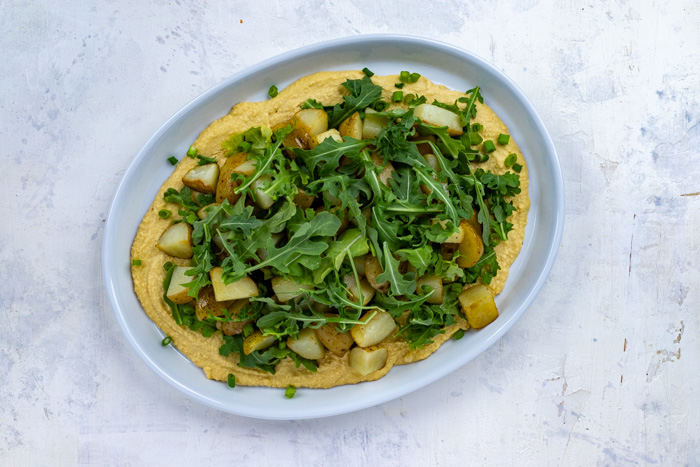 White oval serving tray covered with a layer of hummus topped with arugula leaves and cooked diced potatoes with a final layer of arugula