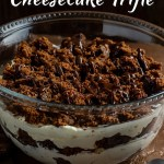 Brownie cheesecake trifle drizzled with hot fudge topping in a glass trifle bowl next to a stainless steel spoon on a wooden surface (with title overlay)
