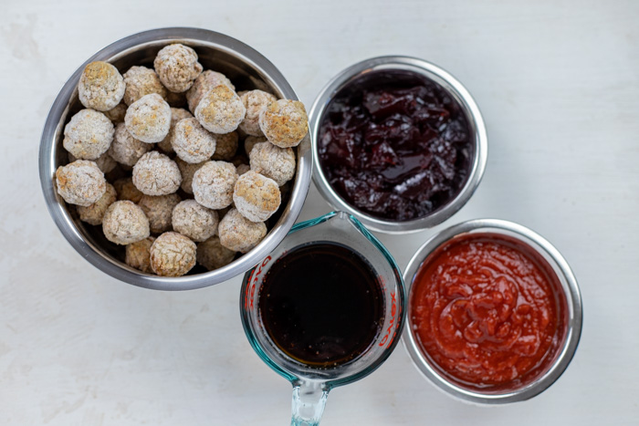 Ingredients for Slow Cooker Swedish Meatballs in stainless steel bowls on a white surface