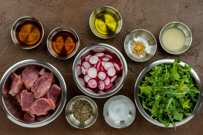 Ingredients for honey glazed pork tenderloin in stainless steel bowls on a brown surface