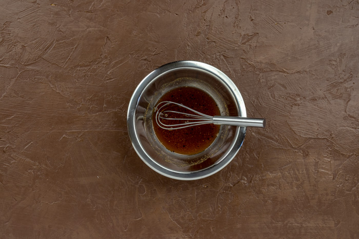 Honey glaze with a small wire whisk in a stainless steel bowl on a brown surface