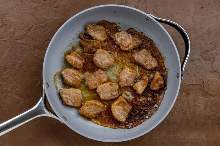 Sliced pork tenderloin with honey glaze in a nonstick skillet on a brown surface
