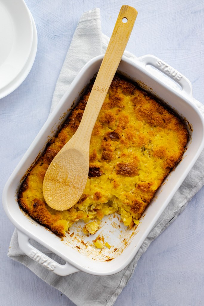 Cooked pineapple bread casserole in a white rectangular baking dish with some removed from the corner with a wooden spoon on top of a white towel with white plates behind all on a light blue surface (vertical)