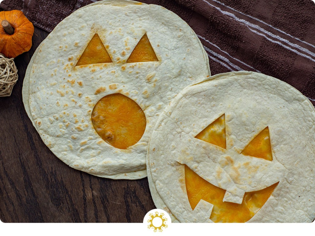 Two Jack-O-Lantern Quesadillas with a brown and white towel behind all on a wooden surface (with logo overlay)