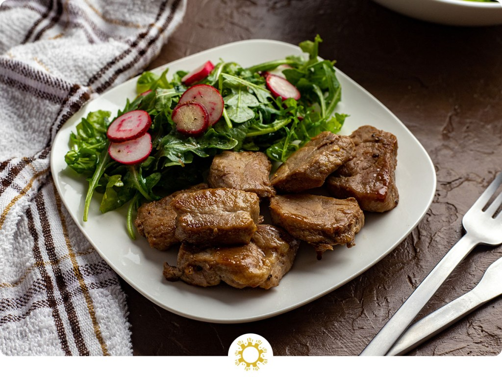 Honey Glazed Pork Tenderloin with Radish Salad on a square white plate with stainless steel forks, a white round bowl of salad behind, and a white and brown towel all on a brown surface (with logo overlay)
