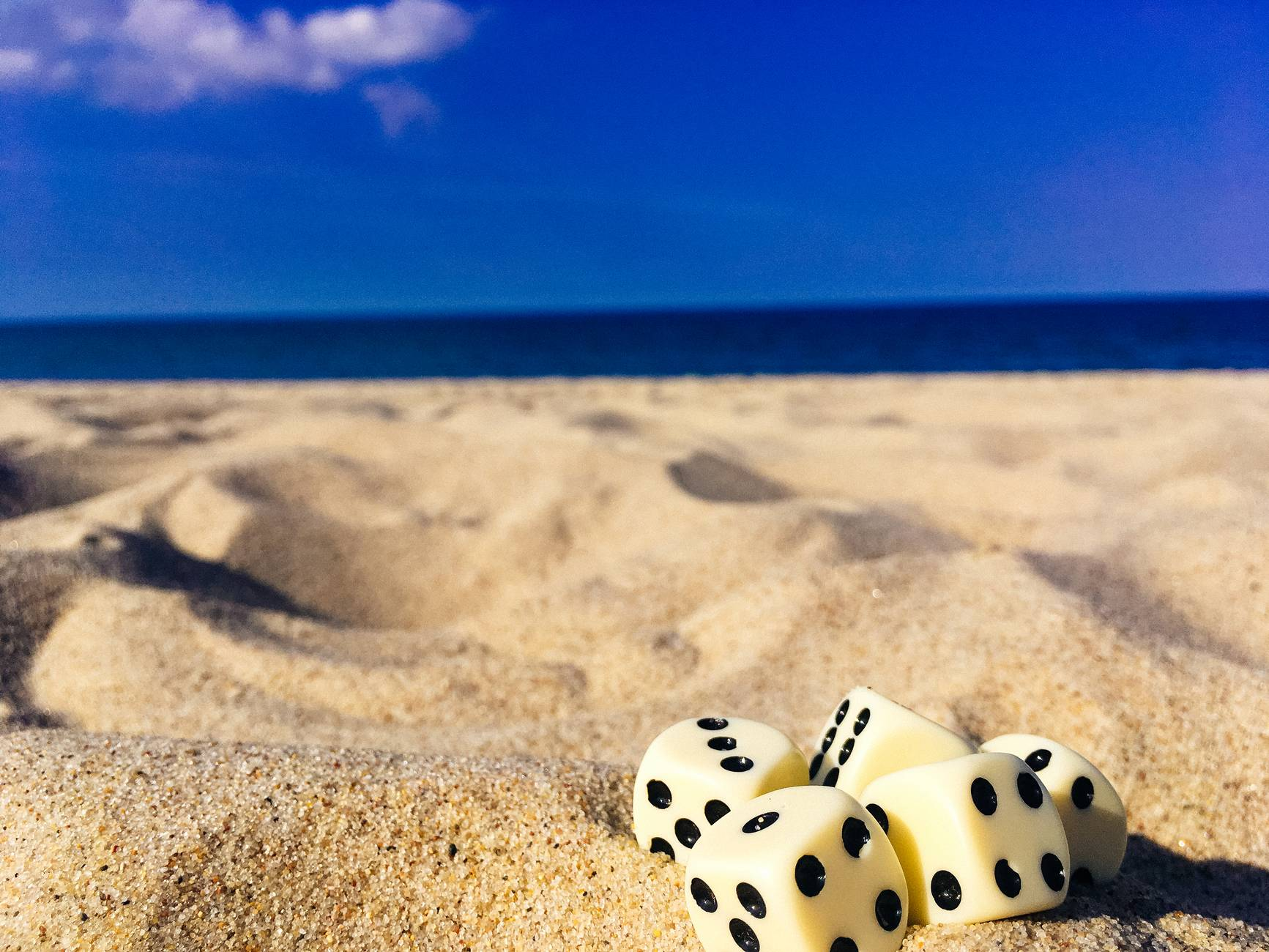 five dice on sand