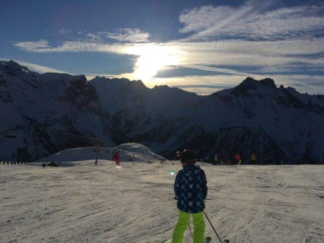 Au premier plan, on voit mon fils de dos sur ses skis prêt à descendre une piste, en second plan, la crête des montagnes et en arrière plan le ciel bleu parsemé de nuages et un soleil en train de se coucher