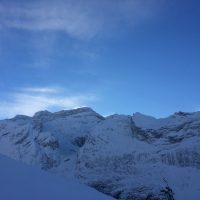 Horizon de montagne enneigée avec un ciel bleu, la neige vole aux cîmes des montagnes