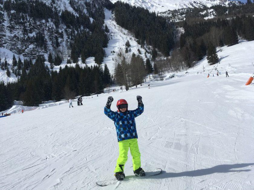 Minipixel les bras en l'air avec un snowboard aux pieds