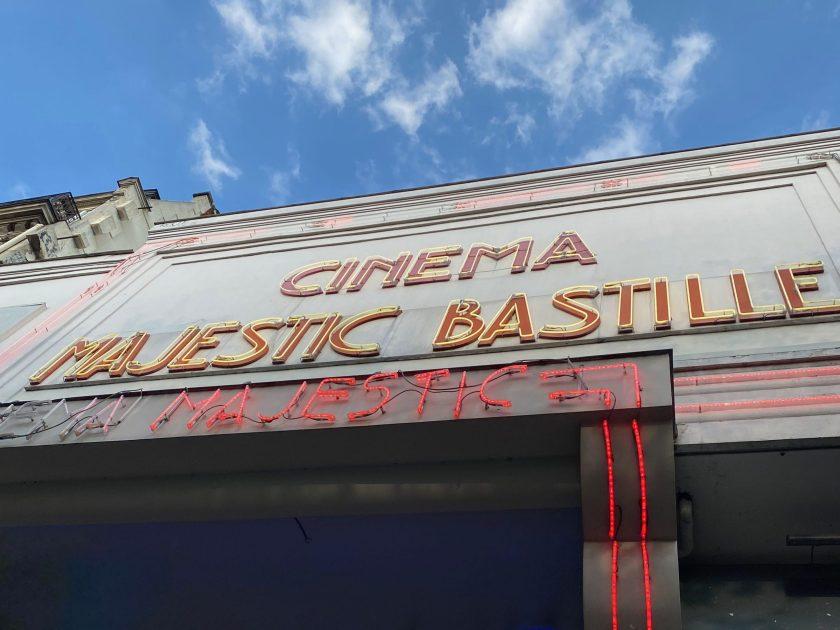 Facade du cinéma, Cinéma Majestic Bastille en néon jaune avec un fond rouge et le ciel bleu en arrière plan.