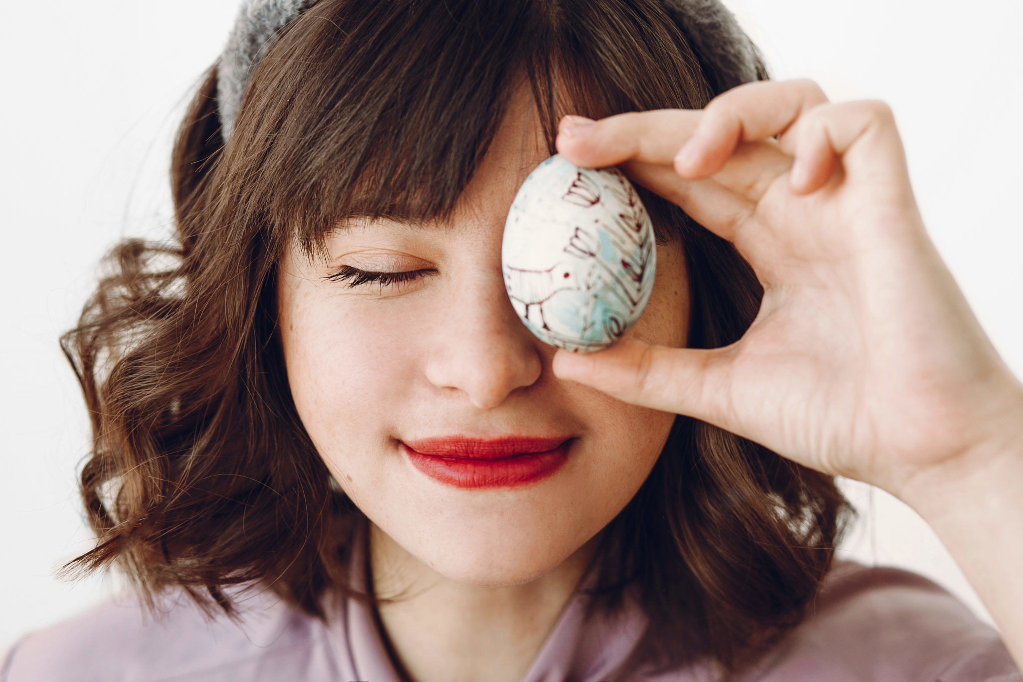 beautiful stylish girl in bunny ears holding easter egg at eyes