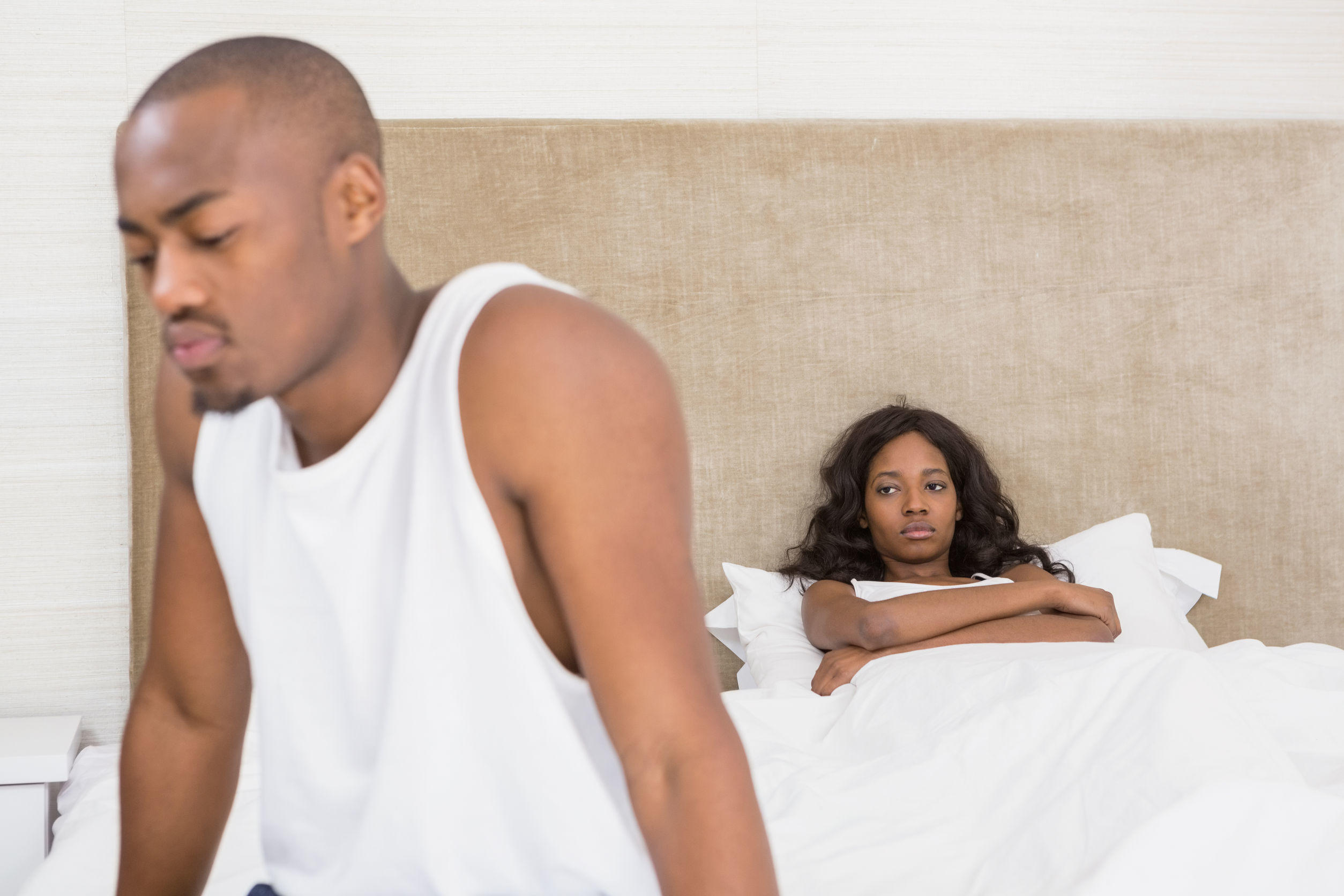 54927629 – young man sitting on bed after an argument in the bedroom