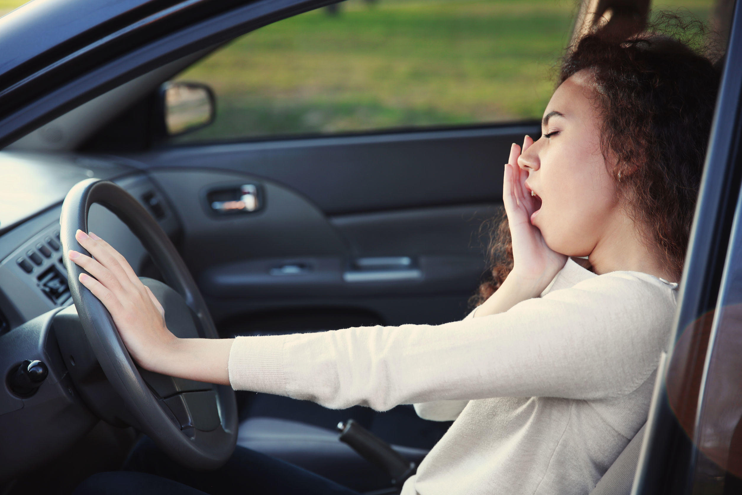 95971900 – a woman feeling sleepy and yawning in the car