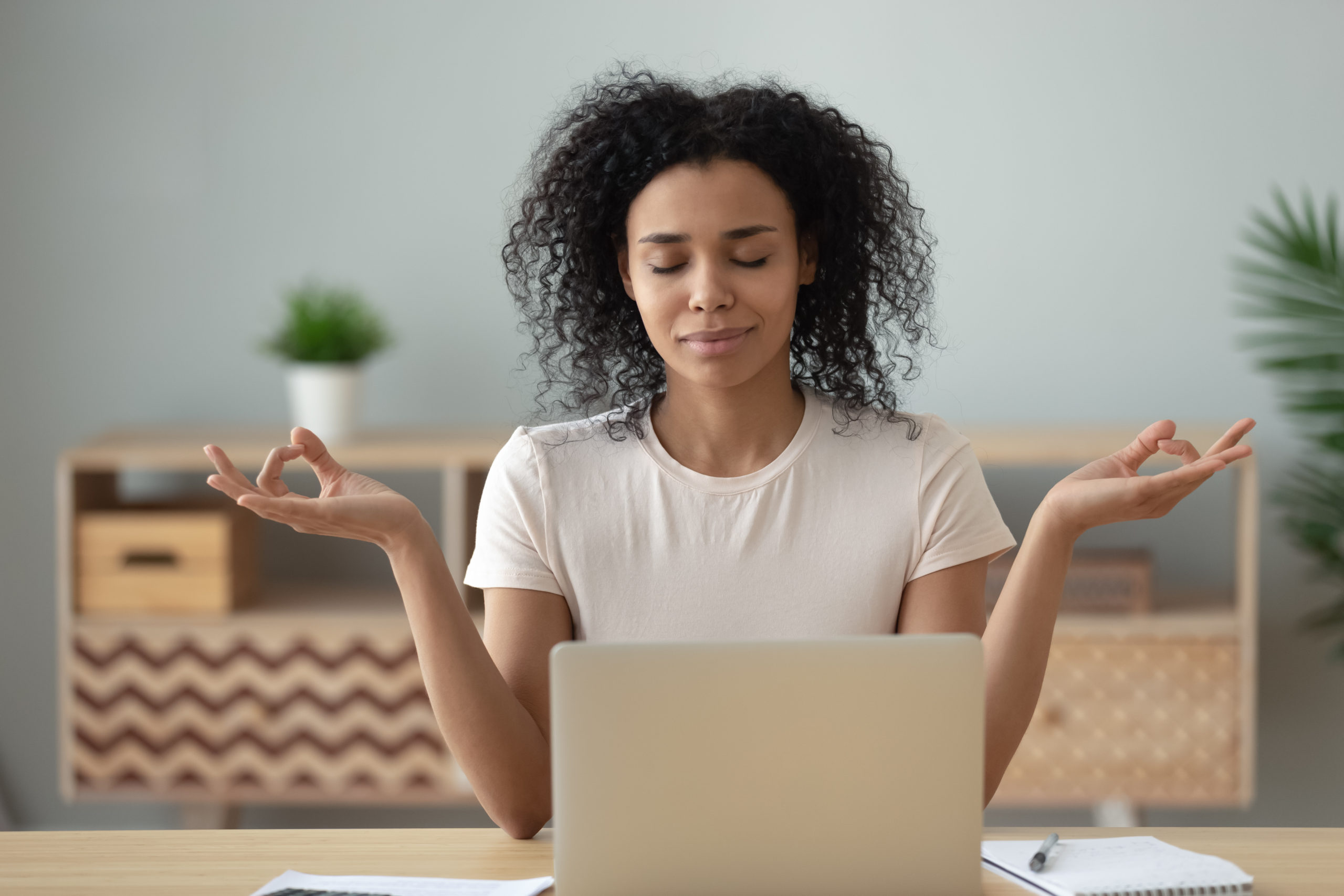 African woman meditating sitting at desk in front of laptop
