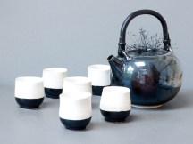 Service à thé en porcelaine, théière noire, 15 cm x 18 cm, émail 'gouttes d'huile', et 6 gobelets en porcelaine noir et blanc, 7,5 cm x 7 cm.