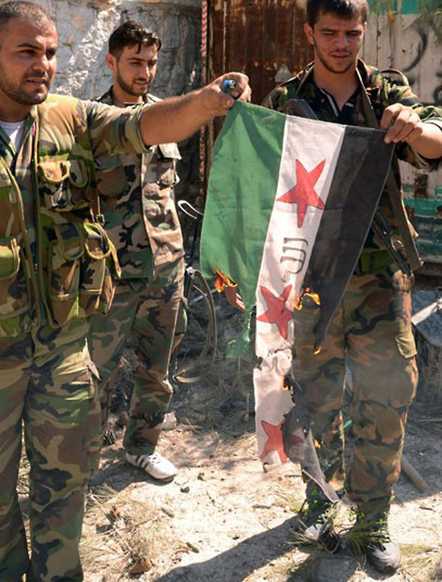 Syrian government troops burn the flag a