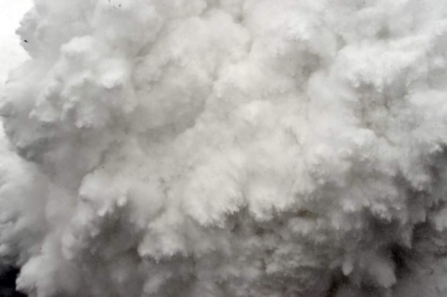 In this photograph taken on April 25, 2015, a cloud of snow and debris triggered by an earthquake flies towards Everest Base Camp, moments ahead of flattening part of the camp in the Himalayas.   Rescuers in Nepal are searching frantically for survivors of a huge quake on April 25, that killed nearly 2,000, digging through rubble in the devastated capital Kathmandu and airlifting victims of an avalanche at Everest base camp.     AFP PHOTO/ROBERTO SCHMIDTROBERTO SCHMIDT/AFP/Getty Images