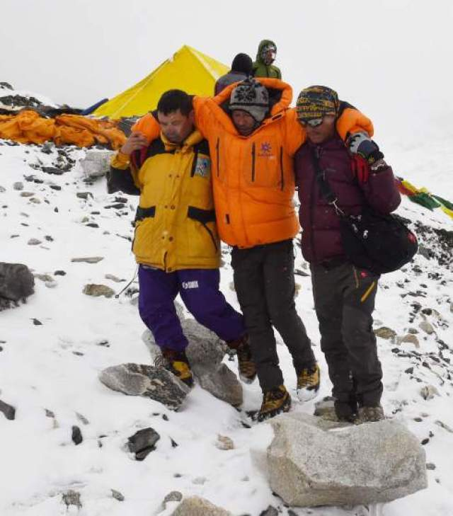 In this photograph taken on April 25, 2015, rescuers assist an injured person after an earthquake triggered by an avalanche flattened parts of Everest Base Camp.   Rescuers in Nepal are searching frantically for survivors of a huge quake on April 25, that killed nearly 2,000, digging through rubble in the devastated capital Kathmandu and airlifting victims of an avalanche at Everest base camp.   AFP PHOTO/Roberto SCHMIDTROBERTO SCHMIDT/AFP/Getty Images