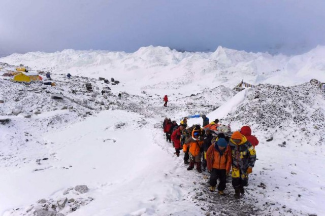 An injured person is carried by rescue members to be airlifted by rescue helicopter at Everest Base Camp on April 26, 2015, a day after an avalanche triggered by an earthquake devastated the camp. Rescuers in Nepal are searching frantically for survivors of a huge quake on April 25, that killed nearly 2,000, digging through rubble in the devastated capital Kathmandu and airlifting victims of an avalanche at Everest base Camp. The bodies of those who perished lie under orange tents. AFP PHOTO/ROBERTO SCHMIDTROBERTO SCHMIDT/AFP/Getty Images