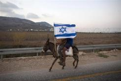Jewish youths hold an Israeli flag as they ride a donkey during a rally march outside the West Bank settlement of Itamar, near Nablus