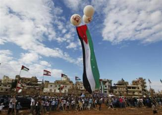 A Palestinian flag attached to balloons flies during a rally in support of Palestinian President Abbas' bid for statehood recognition in the United Nations, in Beirut