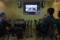 Palestinians watch a TV broadcast of Palestinian President Abbas' speech about his bid for Palestinian statehood recognition at UN, in Herbon
