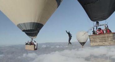 Unos loquillos intentan caminar en una cuerda floja colocada entre globos aerostáticos