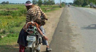 Padre amarra a su hija a una moto para llevarla a la escuela