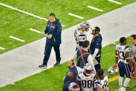 Tom Brady charla con su coordinador ofensivo, Josh McDaniels, antes de que inicien los tiempos extra