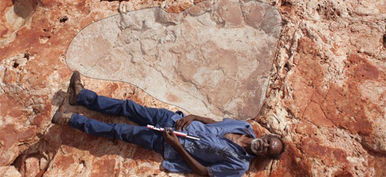 Hombre posando junto a la huella de dinosaurio más grande de la que se tenga registro