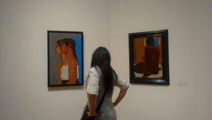 Mujer observando dos pinturas en Bellas Artes.