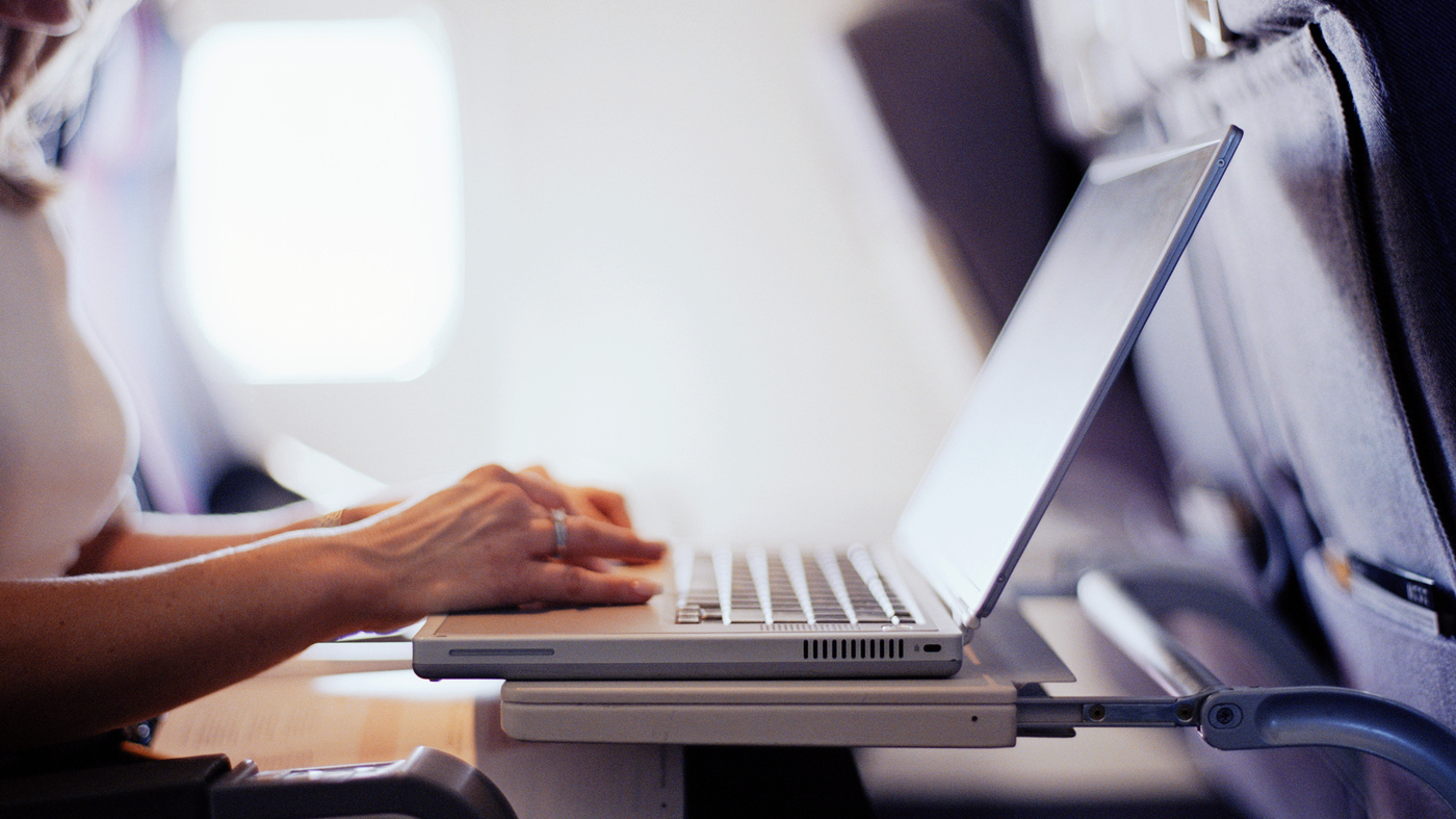 Woman typing on a laptop computer in a commercial airplane.