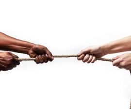 manos de distintos colores jalando una cuerda