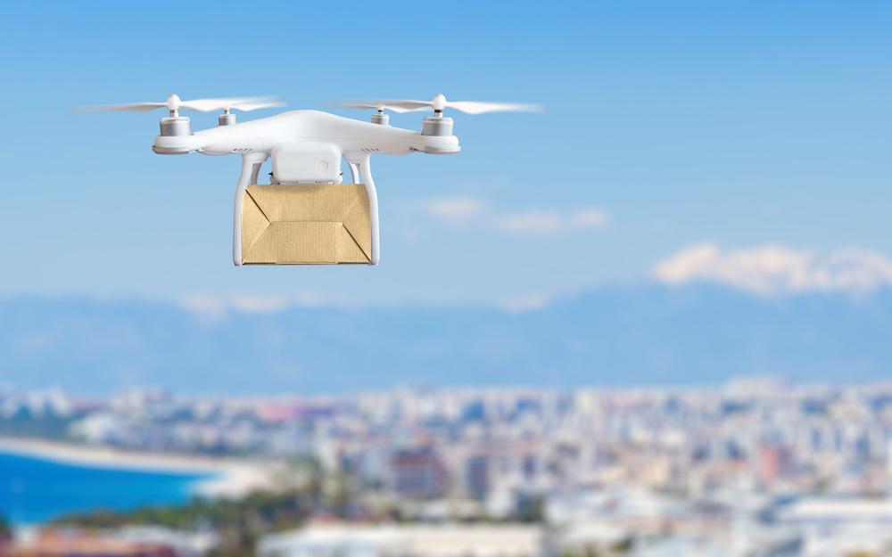 Dron sobrevolando ciudad con paquete