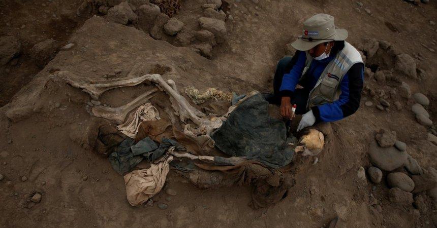 arqueólogo con uno de los cuerpos hallados