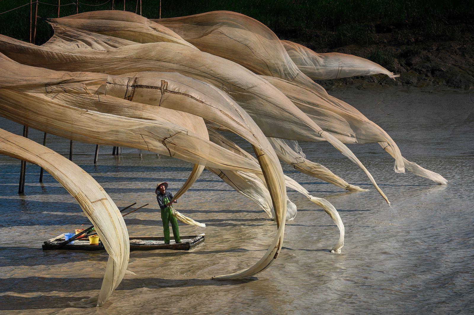 Pescador rodeado de redes