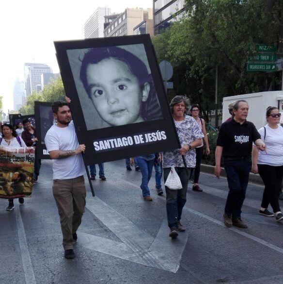 Foto: Roberto Zavala, de playera blanca, cargado la foto de su hijo.