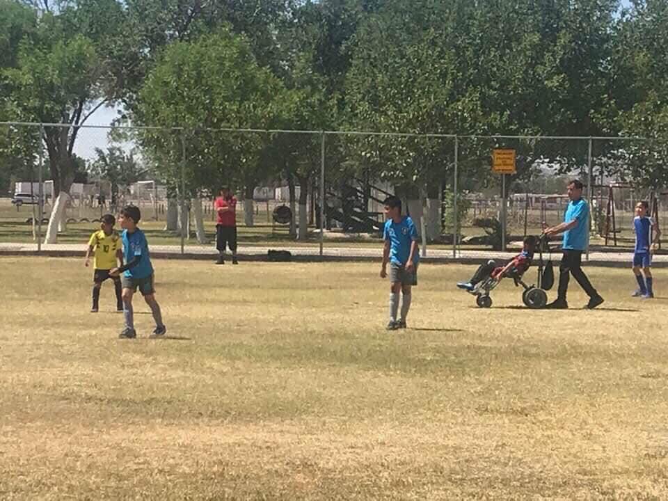 Papá empuja la silla de ruedas de su hijo para que pueda jugar futbol con sus amigos