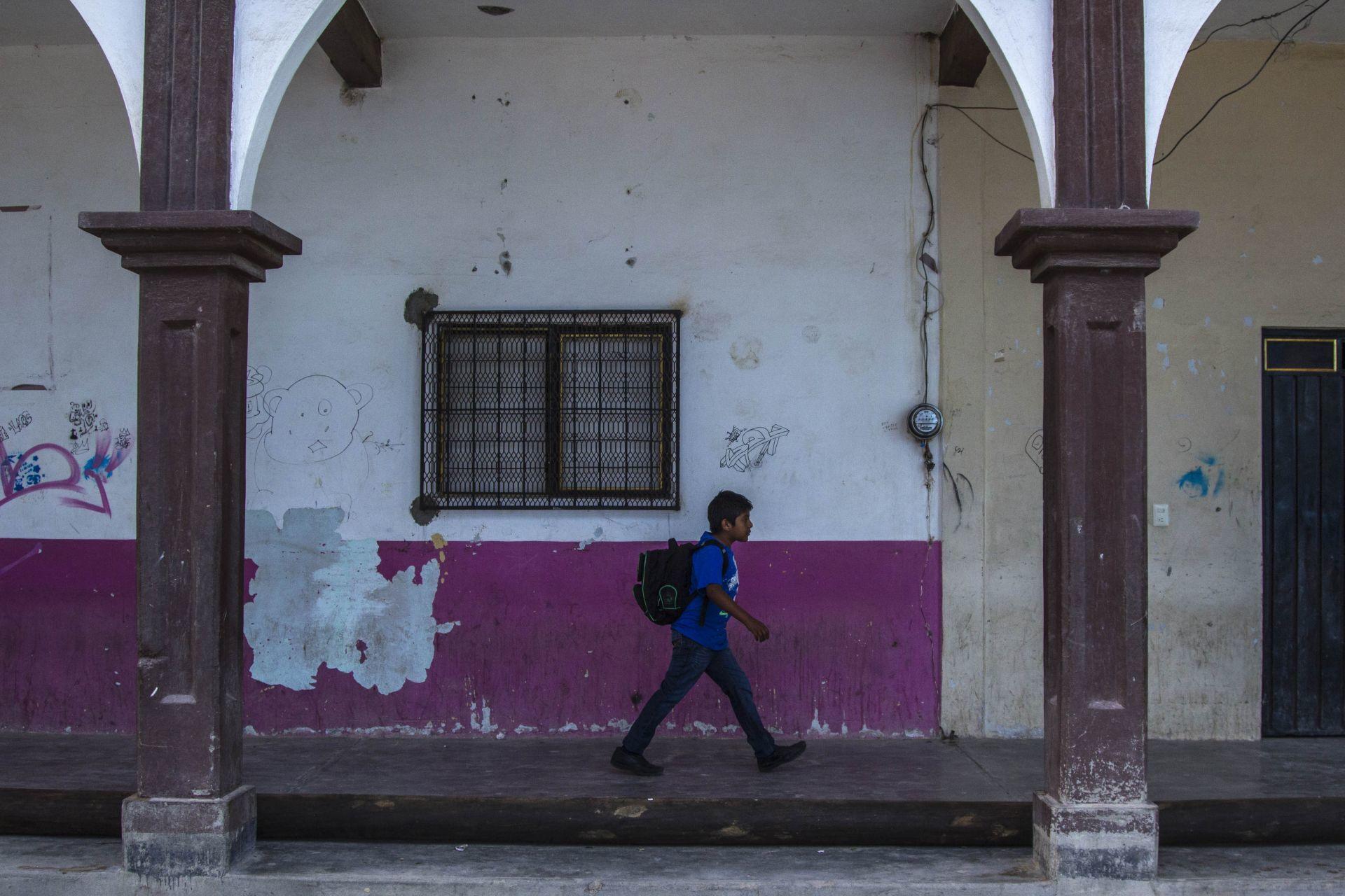 """SANTA CRUZ XITLA, OAXACA, 29AGOSTO, 2015.- La escuela primaria """"Benito Juárez Bilingüe""""  y la Escuela Secundaria Técnica 169, ubicadas a mas de dos horas de la capital del estado pertenecientes a las sección 59 del Coordinadora Nacional de Trabajadores de la Educación (CNTE), tienen carencias por el abandono de parte de la Secretaria de Educación (SEP), ya que  actualmente las aulas son costeadas por padres de familia y algunos maestros interesados en la educación de los menores. Los alumnos tuvieron que dejar las antiguas instalaciones, que se ubican a unos cien metros del nuevo plantel, cuando los padres de familia no pudieron pagar el millón de pesos que solicitó el propietario del terreno. Con una cooperación de mil pesos por niño se logró la adquisición del nuevo espacio donde los menores estudian en aulas de paredes de carrizo y techos de lámina haciéndolos muy vulnerables a las condiciones climáticas de la zona. Sin embargo, cada ciclo escolar los padres de familia en conjunto con los maestros hacen una reunión para planear la forma en que impartirán su educación. A pesar de la Reforma Educativa implementada por el Presidente Enrique Peña Nieto, que busca mejorar la educación a nivel nacional, algunos de los estados mayormente afectados son Oaxaca, Guerrero y Chiapas principalmente en las zonas de la sierra donde los recursos económicos por parte del Gobierno Federal nunca llegan para abatir este problema, además de enfrentarse a los conflictos entre la CNTE y SNTE que perjudican principalmente a los niños que solo buscan adquirir los conocimientos que forman a cada individuo en México.FOTO: ENRIQUE ORDOÑEZ /CUARTOSCURO.COM"""