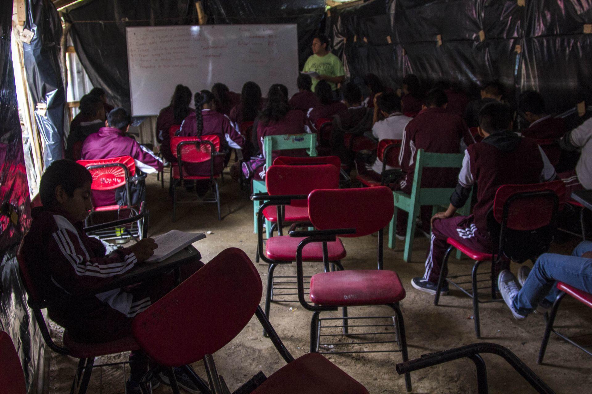 """SANTA CRUZ XITLA, OAXACA, 29AGOSTO, 2015.- La escuela primaria """"Benito Juárez Bilingüe""""  y la Escuela Secundaria Técnica 169, ubicadas a mas de dos horas de la capital del estado pertenecientes a las sección 59 del Coordinadora Nacional de Trabajadores de la Educación (CNTE), tienen carencias por el abandono de parte de la Secretaria de Educación (SEP), ya que  actualmente las aulas son costeadas por padres de familia y algunos maestros interesados en la educación de los menores. Los alumnos tuvieron que dejar las antiguas instalaciones, que se ubican a unos cien metros del nuevo plantel cuando los padres de familia no pudieron pagar el millón de pesos que solicitó el propietario del terreno. Con una cooperación de mil pesos por alumnos se logró la adquisición del nuevo espacio donde los menores estudian en aulas de paredes de carrizo y techos de lámina haciéndolos muy vulnerables a las condiciones climáticas de la zona. Sin embargo cada ciclo escolar, los padres de familia en conjunto con los maestros hacen una reunión para planear la forma en que impartirán su educación. A pesar de la Reforma Educativa implementada por el Presidente Enrique Peña Nieto, que busca mejorar la educación a nivel nacional, algunos de los estados mayormente afectados son Oaxaca, Guerrero y Chiapas principalmente en las zonas de la sierra donde los recursos económicos por parte del Gobierno Federal nunca llegan para abatir este problema, además de enfrentarse a los conflictos entre la CNTE y SNTE que perjudican principalmente a los niños que solo buscan adquirir los conocimientos que forman a cada individuo de la nación.FOTO: ENRIQUE ORDÓÑEZ /CUARTOSCURO.COM"""