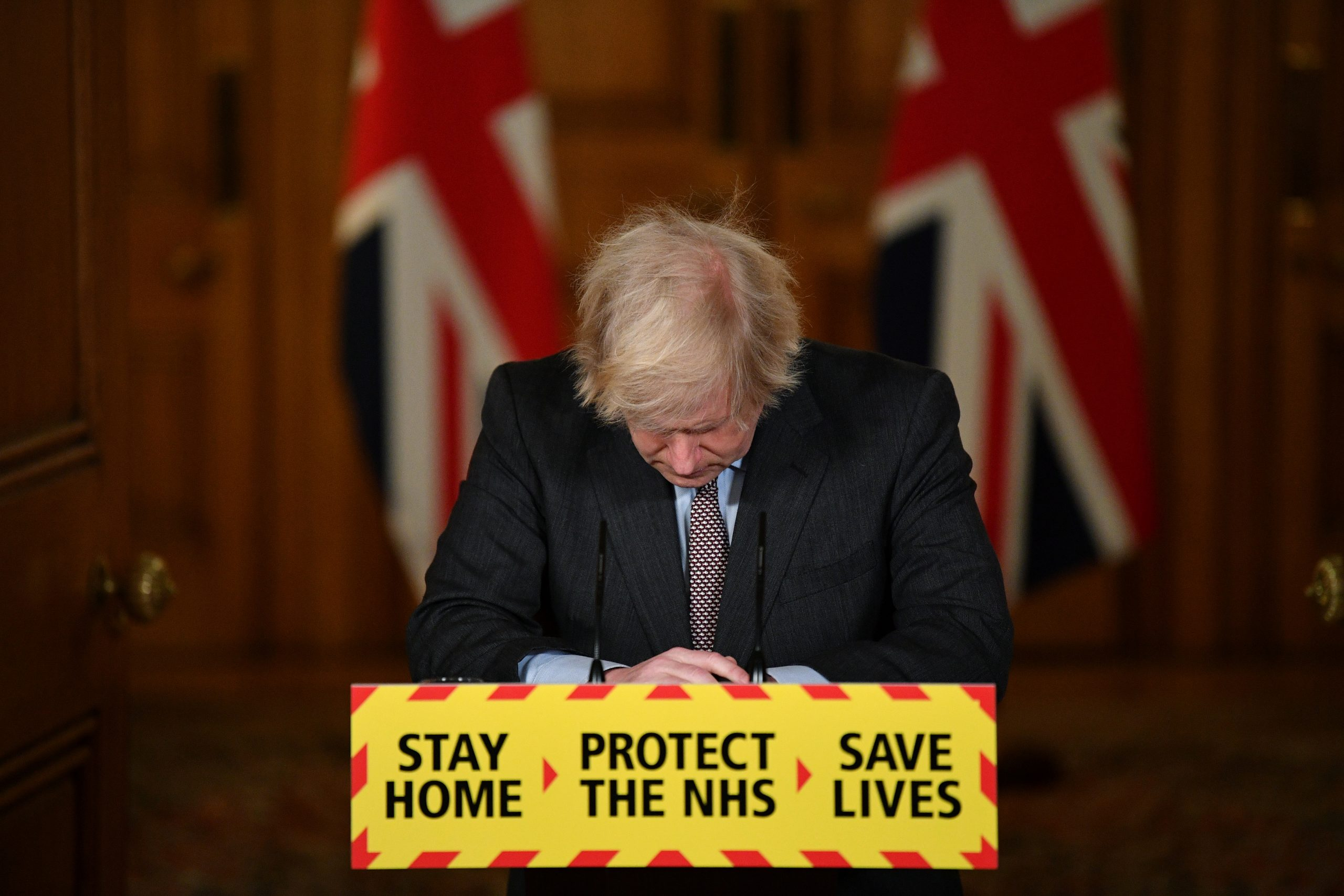 Britain's Prime Minister Boris Johnson looks down at the podium as he attends a virtual news conference on the COVID-19 pandemic inside 10 Downing Street in London, Britain January 26, 2021.
