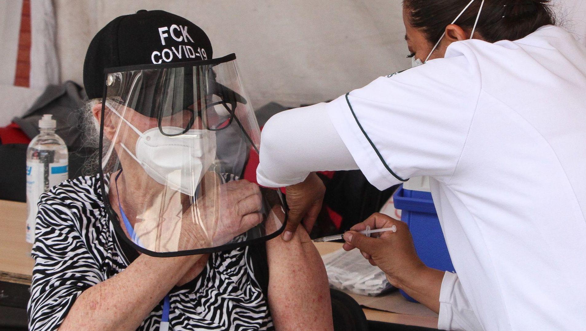 Mujer mayor recibe la vacuna contra el COVID