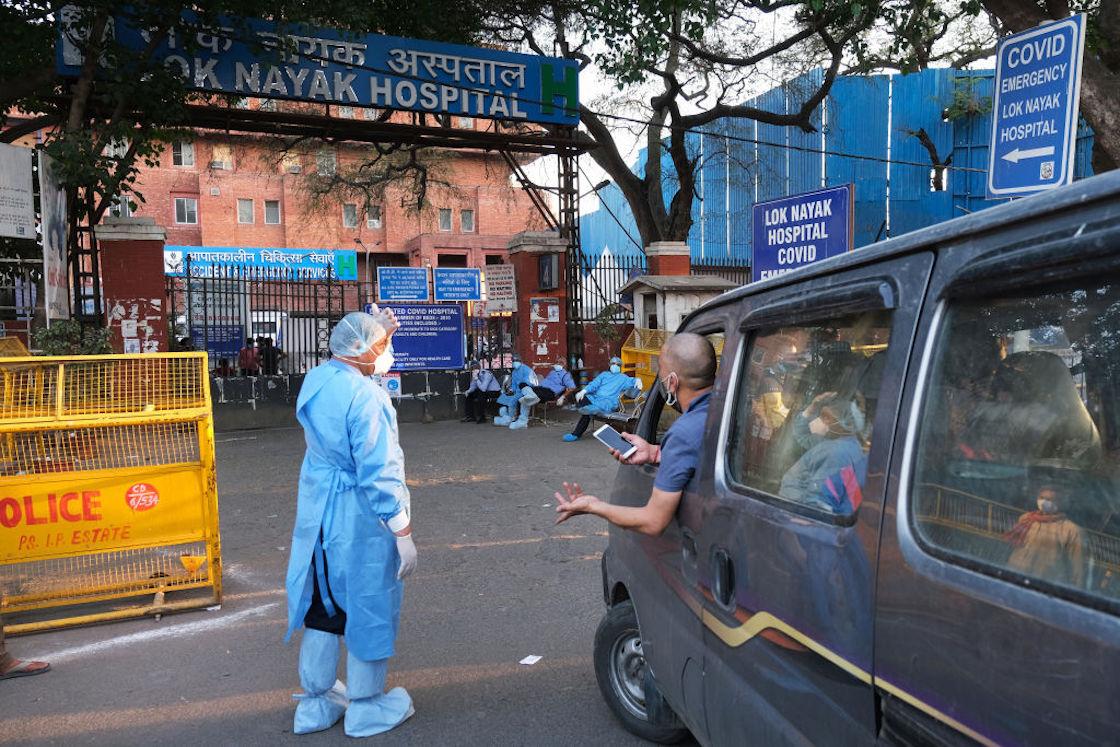 """""""Trabajadores de la salud rechazan un vehículo en la entrada principal del Hospital Lok Nayayak Jaiprakash en Nueva Delhi, India, el domingo 25 de abril de 2021""""."""
